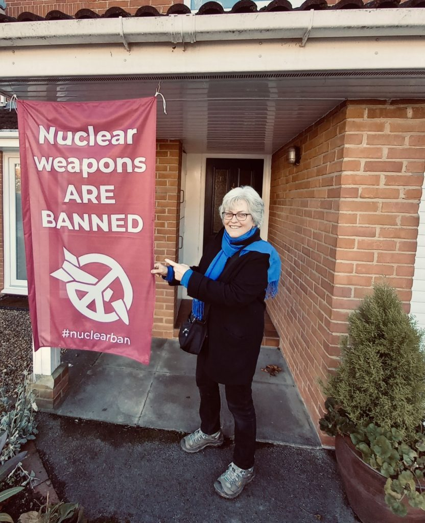 "MAW Vice Chair Hilary Evans with banner, ""Nuclear Weapons ARE BANNED"""